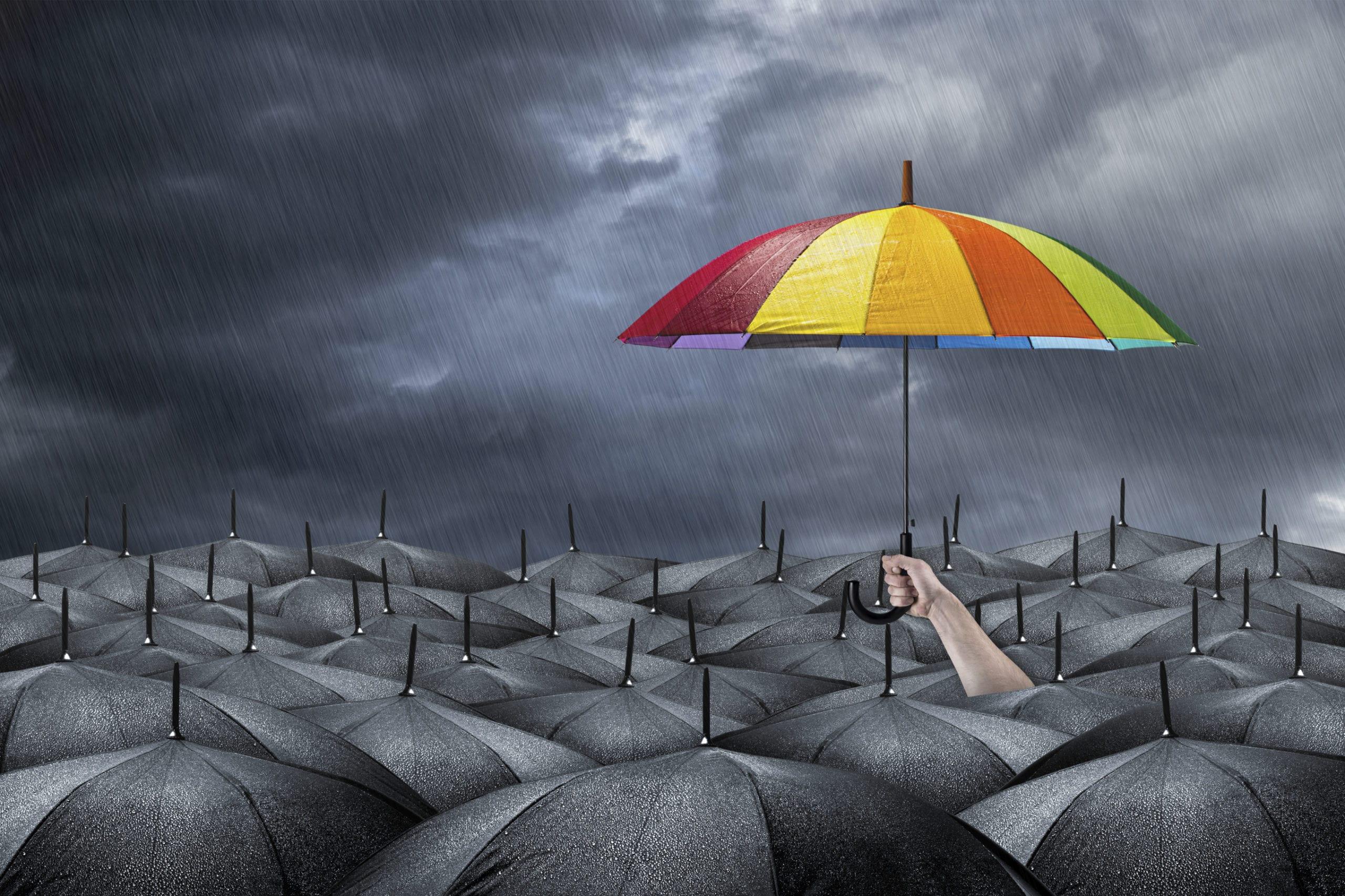 rainbow umbrella in mass of black umbrellas